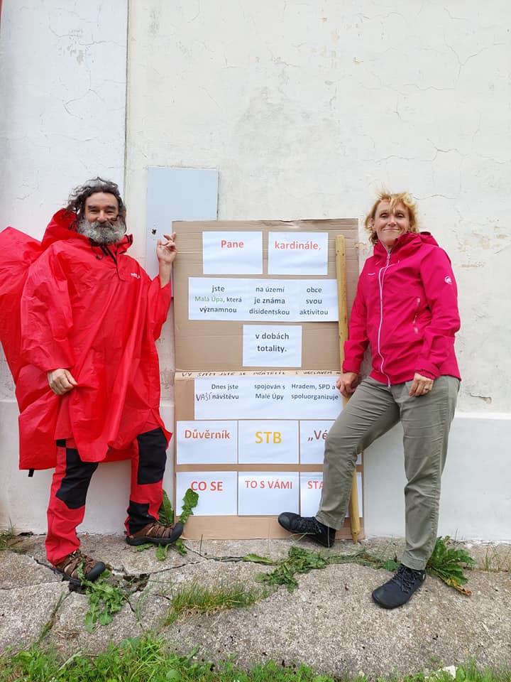 Dwoje ludzi, mężczyzna z lewej ikobieta z prawej stoją koło tablicy z inforamcją, ze wydarzenie zorganizował były wspólpracownik StB